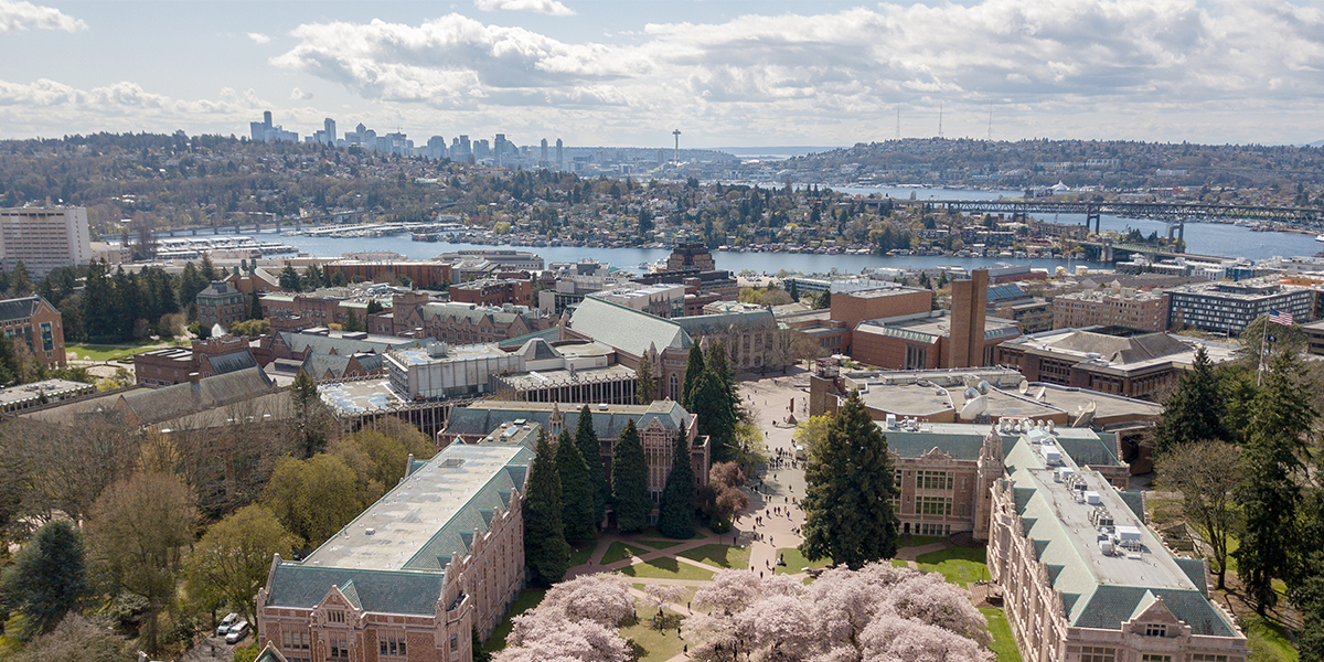 aerial shot of UW facing south to downtown Seattle with cherry blossoms in view